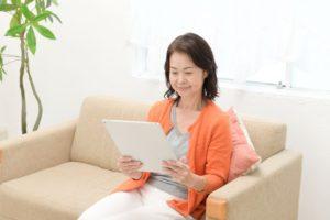 レンタルしたiPadでネットを閲覧する女性